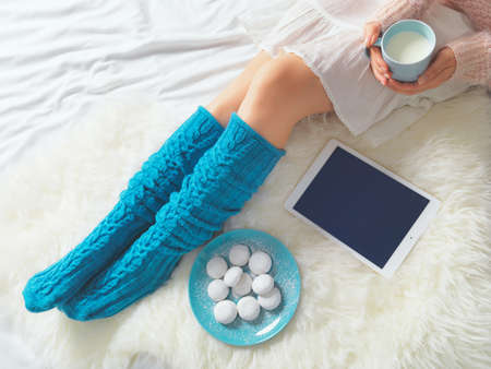 Woman using tablet at cozy home atmosphere on the bed. Young woman with cup of milk in hands enjoying free time with comfort. Soft light and comfy lifestyle concept. Technology in everyday life.