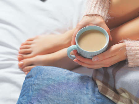 comfy: Woman relaxing at cozy home atmosphere on the bed. Young woman with beautiful skin and nails with cup of cocoa or coffee in her hands enjoying comfort. Soft light and comfy beauty natural lifestyle.