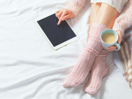 Woman using tablet at cozy home atmosphere on the bed. Young beautiful woman enjoying free time using technological device, holding a cup of cocoa or coffee. Soft light Stockfoto