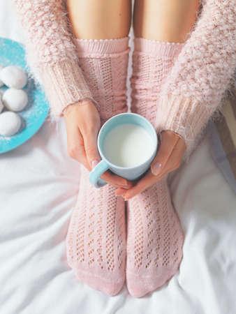 cama: Mujer que se relaja en el acogedor ambiente de casa en la cama. Mujer joven con la taza de leche en las manos y las galletas que disfrutan de la comodidad. La luz suave y el concepto de estilo de vida cómodo.