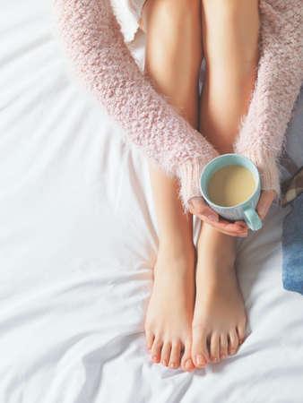 lifestyle: Frau entspannt in einer gemütlichen Atmosphäre zu Hause auf dem Bett. Junge Frau mit schönen Haut und Nägel mit Tasse Kakao oder Kaffee in der Hand genießen Komfort. Weiches Licht und bequeme Schönheit natürlichen Lebensstil.