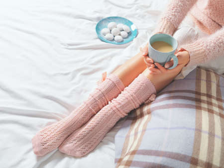 Woman relaxing at cozy home atmosphere on the bed. Young woman with cup of coffee or cocoa in hands and cookies enjoying comfort. Soft light and comfy lifestyle concept.
