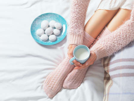 Woman relaxing at cozy home atmosphere on the bed. Young woman with cup of milk in hands and cookies enjoying comfort. Soft light and comfy lifestyle concept. Standard-Bild