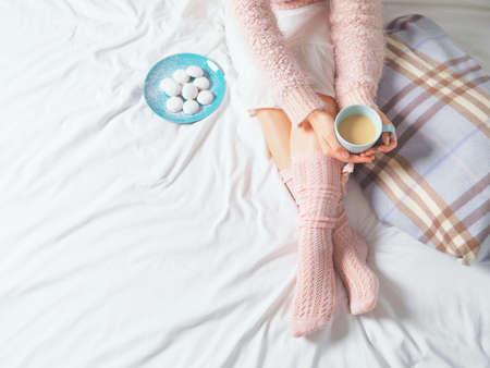stile di vita: Donna che si distende in una struttura accogliente atmosfera di casa sul letto. Giovane donna con la tazza di caffè o il cacao in mano e biscotti che godono il comfort. Luce soffusa e concetto di lifestyle confortevole.