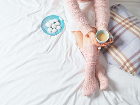 lifestyle: Woman relaxing at cozy home atmosphere on the bed. Young woman with cup of coffee or cocoa in hands and cookies enjoying comfort. Soft light and comfy lifestyle concept.