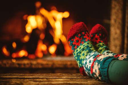 Voeten in wollen sokken bij de open haard. Vrouw ontspant door het warme vuur en opwarmen haar voeten in wollen sokken. Close-up op de voeten. Winter en kerstvakantie concept. Stockfoto