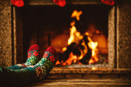 relaxation: Feet in woollen socks by the fireplace. Woman relaxes by warm fire and warming up her feet in woollen socks. Close up on feet. Winter and Christmas holidays concept.