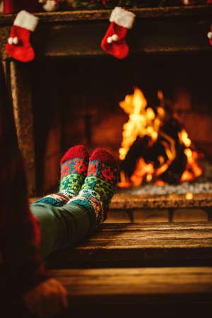 calcetas: Pies en calcetines de lana junto a la chimenea. La mujer se relaja por el fuego caliente y calentar sus pies en calcetines de lana. Cerca de los pies. Invierno y vacaciones de Navidad concepto. Foto de archivo