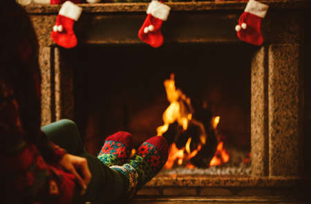 unrecognisable person: Feet in woollen socks by the fireplace. Woman relaxes by warm fire and warming up her feet in woollen socks. Close up on feet. Winter and Christmas holidays concept.