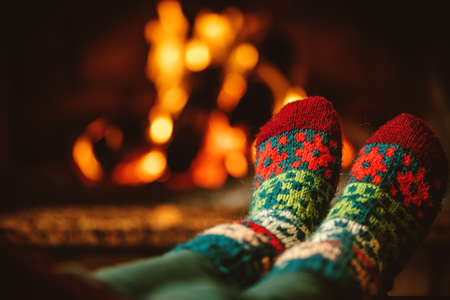 Feet in woollen socks by the fireplace. Woman relaxes by warm fire and warming up her feet in woollen socks. Close up on feet. Winter and Christmas holidays concept.