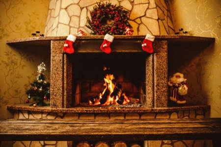 camino natale: Caldo camino decorato per il Natale con vero legno brucia in esso. Concetto di Natale accogliente. Sfondo Natale con spazio per il testo.