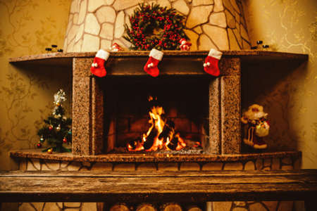 burning fireplace: Warm cozy fireplace decorated for Christmas with real wood burning in it. Cozy Christmas concept. Christmas background with space for your text.