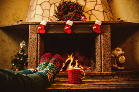 christmas fireplace: Feet in woollen socks by the Christmas fireplace. Woman relaxes by warm fire with a cup of hot drink and warming up her feet in woollen socks. Close up on feet. Winter and Christmas holidays concept. Stock Photo