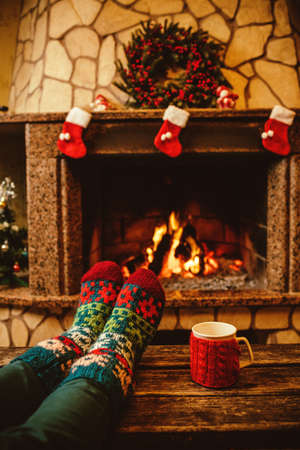 christmas sock: Feet in woollen socks by the Christmas fireplace. Woman relaxes by warm fire with a cup of hot drink and warming up her feet in woollen socks. Close up on feet. Winter and Christmas holidays concept. Stock Photo