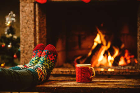 Feet in woollen socks by the Christmas fireplace. Woman relaxes by warm fire with a cup of hot drink and warming up her feet in woollen socks. Close up on feet. Winter and Christmas holidays concept. Standard-Bild