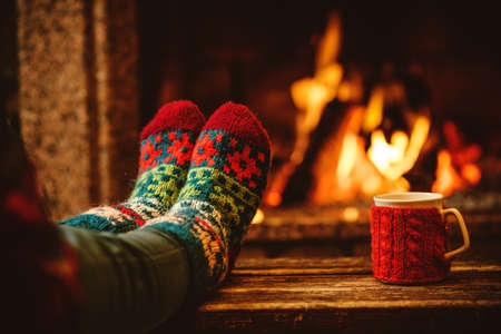 Feet in woollen socks by the Christmas fireplace. Woman relaxes by warm fire with a cup of hot drink and warming up her feet in woollen socks. Close up on feet. Winter and Christmas holidays concept. Stok Fotoğraf