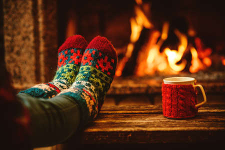 Feet in woollen socks by the Christmas fireplace. Woman relaxes by warm fire with a cup of hot drink and warming up her feet in woollen socks. Close up on feet. Winter and Christmas holidays concept. Banco de Imagens