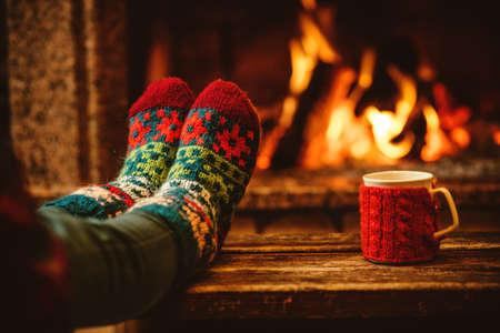 navide�os: Pies en calcetines de lana junto a la chimenea de la Navidad. La mujer se relaja por el fuego caliente con una taza de bebida caliente y calentar sus pies en calcetines de lana. Cerca de los pies. Invierno y vacaciones de Navidad concepto.