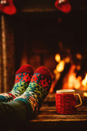 Feet in woollen socks by the Christmas fireplace. Woman relaxes by warm fire with a cup of hot drink and warming up her feet in woollen socks. Close up on feet. Winter and Christmas holidays concept. 스톡 콘텐츠