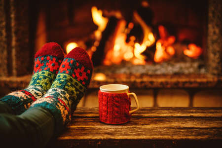 log cabin: Feet in woollen socks by the Christmas fireplace. Woman relaxes by warm fire with a cup of hot drink and warming up her feet in woollen socks. Close up on feet. Winter and Christmas holidays concept. Stock Photo