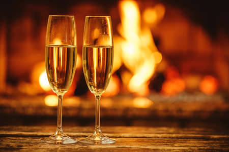 snug: Two glasses of sparkling champagne in front of warm fireplace. Cozy relaxed magical atmosphere in a chalet house by the fireside. Snug holiday concept. Beautiful background with shimmering wine.