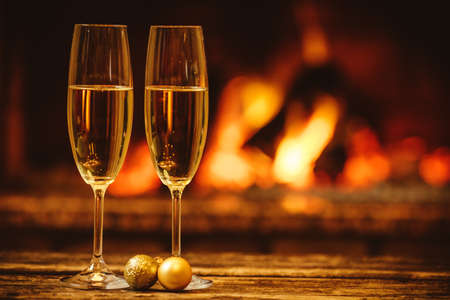 Two glasses of sparkling champagne in front of warm fireplace. Cozy relaxed magical atmosphere in a chalet. Holiday concept. Beautiful background with shimmering wine, decorated with golden baubles.