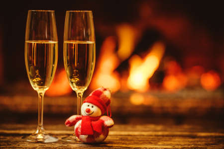 Two glasses of sparkling champagne in front of warm fireplace. Cozy relaxed magical atmosphere in a chalet. Holiday concept. Beautiful background with shimmering wine, decorated with snowman toy. Imagens