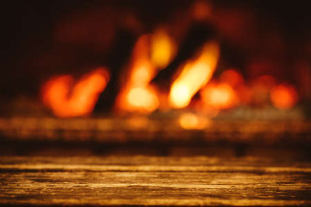 Warm cozy fireplace with real wood burning in it. Cozy evening in chalet concept. Winter and autumn fireside background with space for your text.