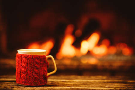 atmosphere: Cup of hot drink in front of warm fireplace. Holiday Christmas concept. Mug in red knitted mitten standing near fireside. Cozy relaxed magical atmosphere in a chalet.