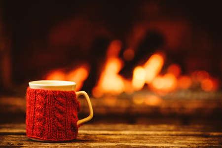 Kop van hete drank in de voorkant van de warme open haard. Concept vakantie Kerst. Mok in rode gebreide want die zich dichtbij open haard. Gezellige ontspannen magische sfeer in een chalet.