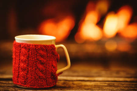 Cup of hot drink in front of warm fireplace. Holiday Christmas concept. Mug in red knitted mitten standing near fireside. Cozy relaxed magical atmosphere in a chalet.