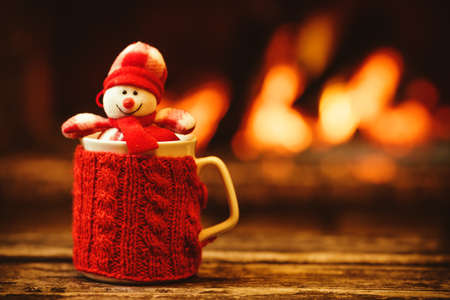 Cup of hot drink in front of warm fireplace. Holiday Christmas concept. Mug in red knitted mitten, decorated with snowman toy, standing near fireside. Cozy relaxed magical atmosphere in a chalet.
