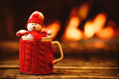 Tasse heißes Getränk vor warmem Kamin. Feiertags-Weihnachtskonzept. Becher im roten Strickhandschuh, verziert mit Schneemannspielzeug, in der Nähe des Kamins. Gemütliche entspannte magische Atmosphäre in einem Chalet.