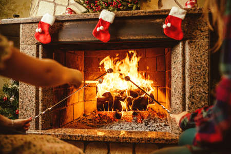 fireplace home: Family roasting marshmallows by the fire. Cozy chalet home with fireplace decorated with traditional Christmas ornaments. Cozy relaxed magical atmosphere in a chalet. Holiday concept.