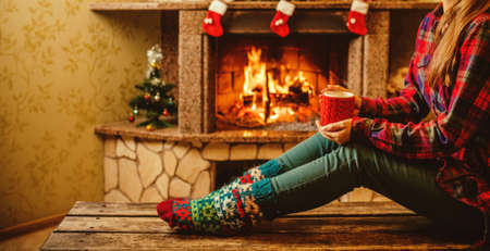 Woman with a mug by the fireplace. Young attractive woman sitting by the fireside and holding a cup with hot drink, enjoying cozy evening. Holiday time concept in a house decorated for Christmas. Imagens