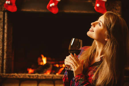 holiday house: Woman with a glass of wine by the fireplace. Young attractive woman sitting by the fireside and holding a wineglass, enjoying cozy evening. Holiday time concept in a house decorated for Christmas.