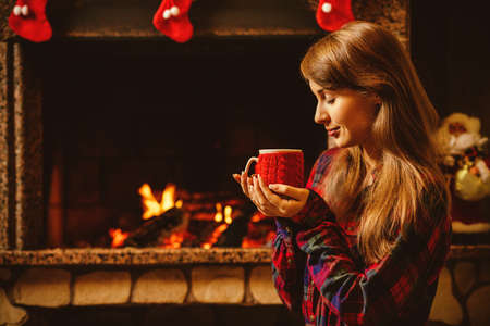 holiday house: Woman with a mug by the fireplace. Young attractive woman sitting by the fireside and holding a cup with hot drink, enjoying cozy evening. Holiday time concept in a house decorated for Christmas. Stock Photo