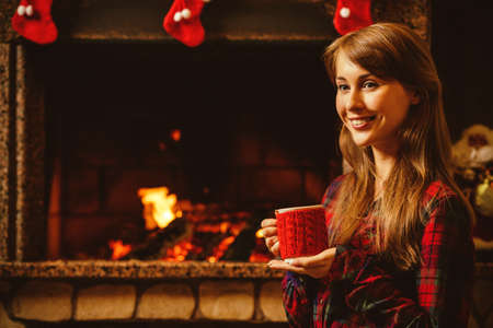 Woman with a mug by the fireplace. Young attractive woman sitting by the fireside and holding a cup with hot drink, enjoying cozy evening. Holiday time concept in a house decorated for Christmas. Standard-Bild