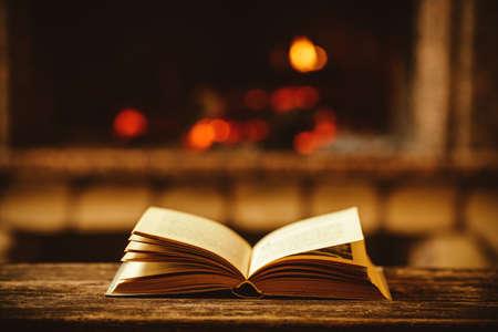 camino natale: Aprire libro davanti al caminetto con addobbi natalizi. Aperto libro di fiabe sdraiato su una panca di legno accanto al fuoco. Accogliente magica atmosfera rilassata in una casa chalet decorato per Natale. Concetto di vacanza.