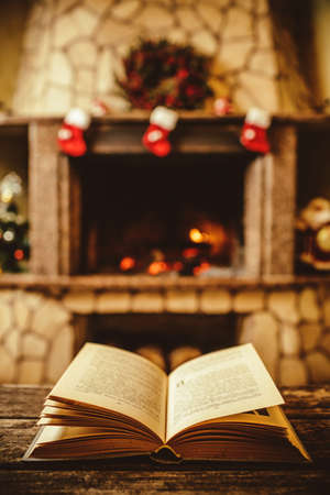 Open book by the Fireplace with Christmas ornaments. Open storybook lying on a wooden bench by the fireside. Cozy relaxed magical atmosphere in a chalet house decorated for Christmas. Holiday concept. Standard-Bild