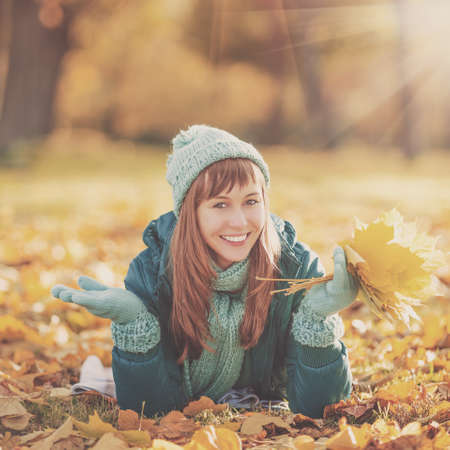 Beautiful happy young woman in the autumn park. Joyful woman wearing bright teal hat and scarf is having fun outdoors in a bright yellow trees. Colorful fall concept. Stock Photo