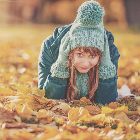 tree  forest: Beautiful happy young woman in the autumn park. Joyful woman wearing bright teal hat and scarf is having fun outdoors in a bright yellow trees. Colorful fall concept. Stock Photo