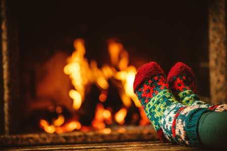 rest and relaxation: Feet in woollen socks by the fireplace. Woman relaxes by warm fire and warming up her feet in woollen socks. Close up on feet. Winter and Christmas holidays concept.