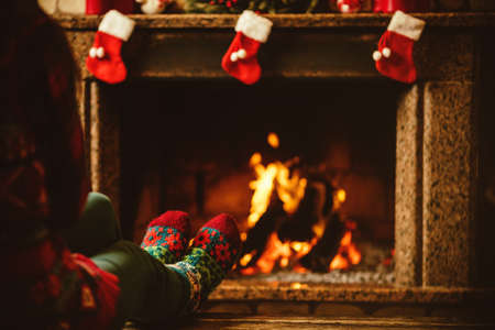 stockings feet: Feet in woollen socks by the fireplace. Woman relaxes by warm fire and warming up her feet in woollen socks. Close up on feet. Winter and Christmas holidays concept.