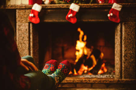 stockings: Feet in woollen socks by the fireplace. Woman relaxes by warm fire and warming up her feet in woollen socks. Close up on feet. Winter and Christmas holidays concept.