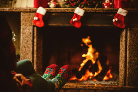 christmas fireplace: Feet in woollen socks by the fireplace. Woman relaxes by warm fire and warming up her feet in woollen socks. Close up on feet. Winter and Christmas holidays concept.
