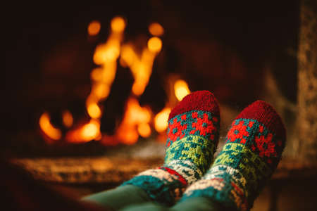 snug: Feet in woollen socks by the fireplace. Woman relaxes by warm fire and warming up her feet in woollen socks. Close up on feet. Winter and Christmas holidays concept.