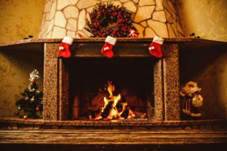 christmas stockings: Warm cozy fireplace decorated for Christmas with real wood burning in it. Cozy Christmas concept. Christmas background with space for your text.