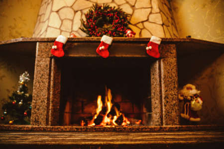 log on: Warm cozy fireplace decorated for Christmas with real wood burning in it. Cozy Christmas concept. Christmas background with space for your text.