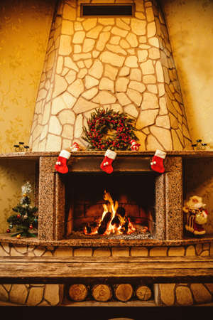 fireplace home: Warm cozy fireplace decorated for Christmas with real wood burning in it. Cozy Christmas concept. Christmas background with space for your text.